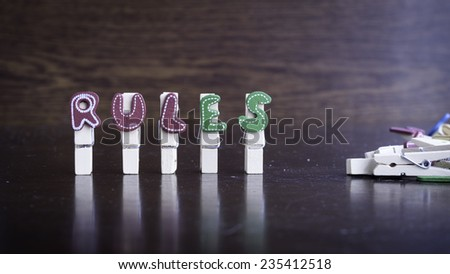 Common business terms - Slightly defocused and close-up of RULES word on clothes peg stick with lots of clothes peg at background