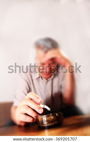 Common elderly man with mustache smoking cigarette