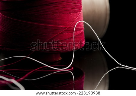 common thread, cotton yarn red and white leaning on black table mirror. reel of cotton spool of red and white cotton blurred in the background - stock photo