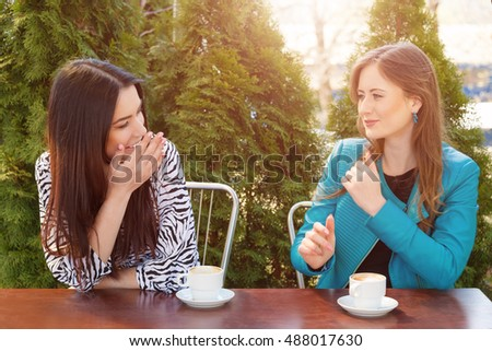 Communication and friendship concept -two girls drinking coffee in a coffee shop terrace looking each other