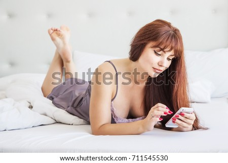 Communication and people lifestyle concept - happy young woman lying in bed with a smart phone at home bedroom. Gray silk pajamas. Beautiful girl