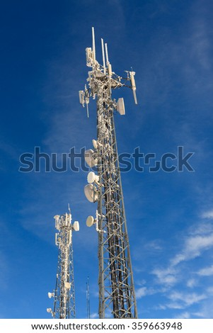 Communication antenna tower ( transmitter )  and bright blue sky in winter time  - stock photo