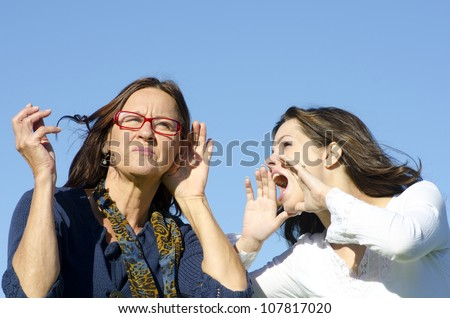 Communication between two women, between two generations, mother and daughter, two friends, one shouting, one listening, with clear blue sky as background and copy space. - stock photo