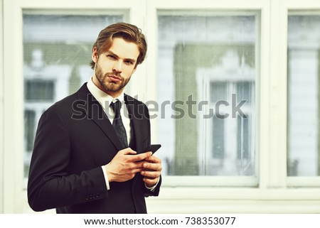 communication. businessman, technology and people concept, serious businessman with smartphone talking in office near window, copy space