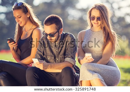 Communication concept. Group of young hipster friends playing with your mobile phones, each for himself. - stock photo