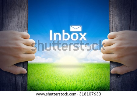 """Communication Concept """"Inbox"""". Hands opening a wooden door then found a texts floating among new world as green grass field, Blue sky and the Sunrise. - stock photo"""