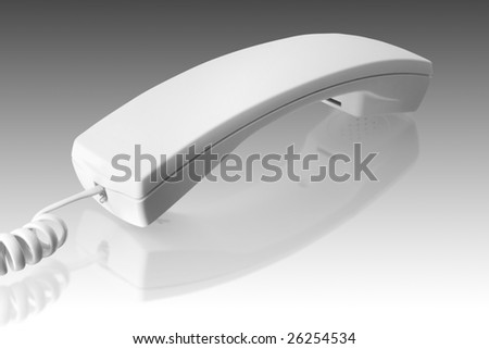 communication object. white telephone handset with reflection
