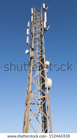 Communication radio tower with devices above blue sky