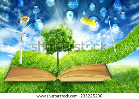 communication technology high tech social media symbol icon fly in green micro world. Book covered with green grass wind energy turbine. Sustainable source electricity concept. Eco friendly approach - stock photo