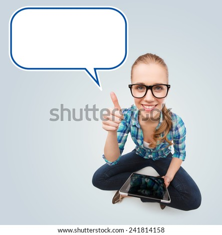 communication, technology, internet, gesture and people concept - smiling teenage girl in eyeglasses holding tablet pc computer and showing thumbs up over gray background with blank white text bubble - stock photo
