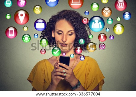 communication technology mobile phone high tech concept. Annoyed skeptical woman using texting on smartphone application icons flying out of cellphone screen isolated grey background. 4g data plan - stock photo