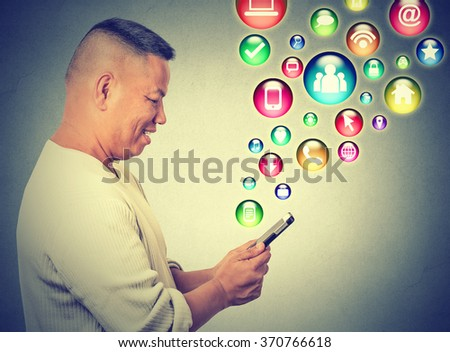 Communication technology mobile phone high tech concept. Side profile happy man using texting on smartphone social media application icons flying out of cellphone isolated grey background. Data plan  - stock photo