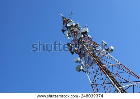 communication tower against blue sky - stock photo