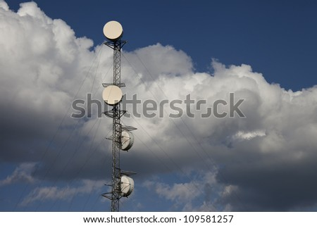 Communication tower completely surrounded by cloudy blue sky. Plenty of room for text.