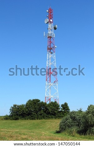 Communication tower over blue sky - stock photo