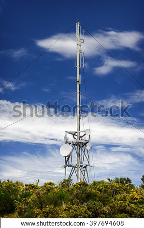 Communication tower radio mast with antenna aerial  against a background of the blue sky. - stock photo