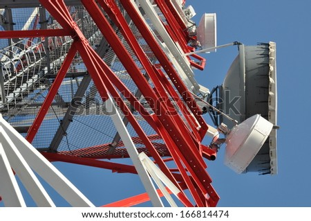 Communication tower with antennas against the blue sky - stock photo