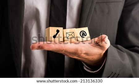 Communications concept with a businessman holding three wooden blocks in his hand depicting a telephone, mail and email for contact, advice , chat and support. - stock photo