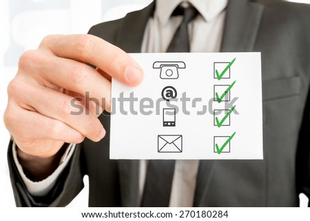 Communications concept with a businessman holding up a checklist with the icons for telephone,email, mobile phone and website ticked with green check marks, close up of his hand holding a card. - stock photo