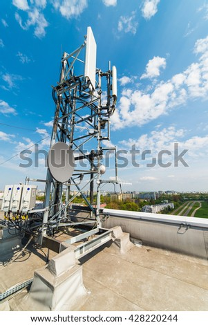 communications mast with antennas on the roof of an office building - stock photo