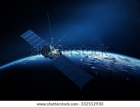Communications satellite orbiting Earth with sunrise in space - stock photo