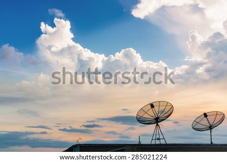 communications signals via a satellite dish over the sky around the world - stock photo