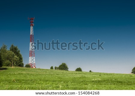 Communications tower at the blue sky and green meadow  - stock photo