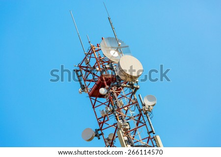 Communications tower with antennas on blue sky - stock photo