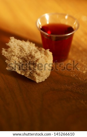 Communion cup with wine and bread - stock photo