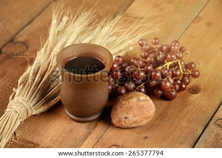 Communion elements with wine and bread on wooden table - stock photo