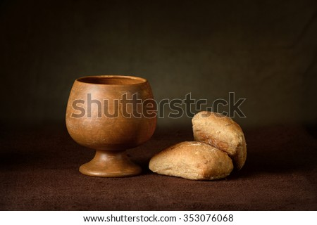 Communion elements with wine cup and bread on table - stock photo
