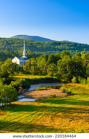 Community Church with a tall steeple in a rural village setting, Stowe, Vermont USA - stock photo