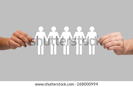 community, unity and teamwork concept - multiracial couple hands holding paper chain people over grey background - stock photo