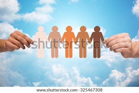 community, unity, population, race and humanity concept - multiracial couple hands holding chain of paper people pictogram over blue sky and clouds background - stock photo