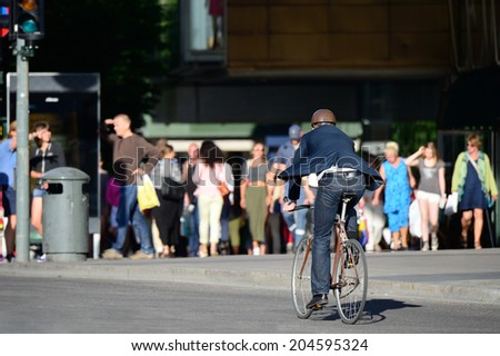 Commuter on bike, in suit - stock photo