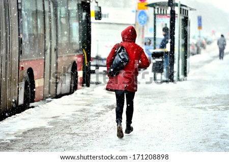 Commuter running to bus in snowstorm - stock photo