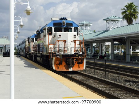 Commuter train arrives on the station - stock photo