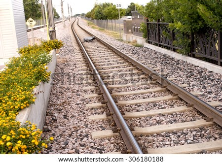 Commuter train tracks leaving train station and curving in the distance - stock photo