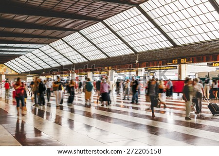 Commuters at the train station. Long exposure. Motion blurred people walking in the station at rush hour.  - stock photo