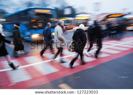 commuters crossing the street at a bus station