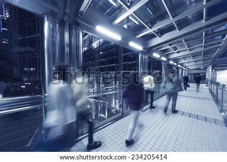 Commuters in pedestrian transition over busy street - stock photo