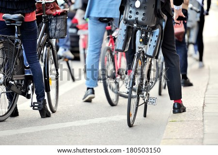 Commuters on bikes waiting for green light - stock photo
