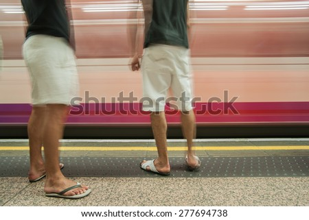 Commuters on platform, motion blur as train speeds past two men waiting for arriving train to stop. - stock photo