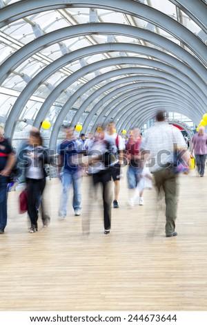 Commuters rushing in corridor, motion blur - stock photo
