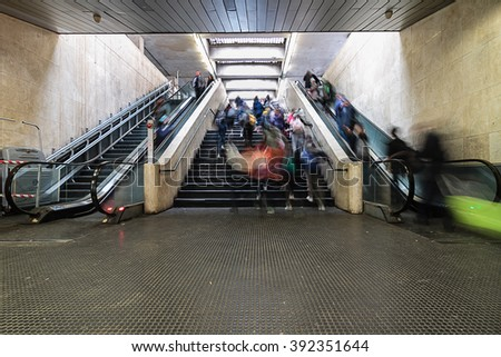 Commuters using escalators at the station. Group of people moving during rush hour. Blurred motion effects due to long exposure. - stock photo