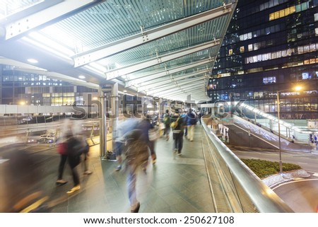 Commuters walking along an elevated walkway in downtown district in Hong Kong - stock photo