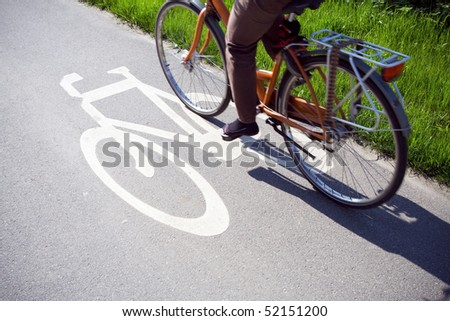 Commuting to work, Blurred woman riding bicycle on a bike path - stock photo
