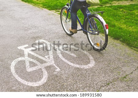 Commuting to work on a bicycle. Woman riding bicycle on a bike path marked with symbol. - stock photo