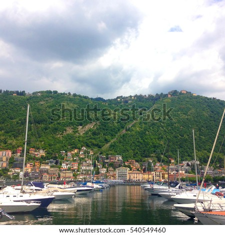 Como, Italy - May 17, 2016: Beautiful nature of Bellagio. Yachts and boats, in row among wonderful nature of sunny Italy. Lake Como is a lake of glacial origin in Lombardy.