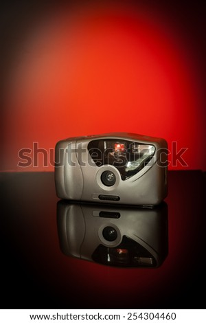 Compact camera photographed on a table in a studio against a red background